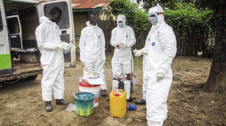 Hjälparbetare i Sierra Leone tar på sig skyddsutrustning innan de går in i ett hus med en ebolasmittad i Freetown. Det är inte den svenske hjälparbetaren som syns på bilden. Foto: Michael Duff