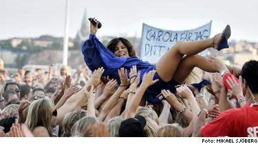 Carola slänger sig ut i vimlet i sin blåa skrud. Jag är inte rädd för att kasta mig ut i publiken, säger hon.