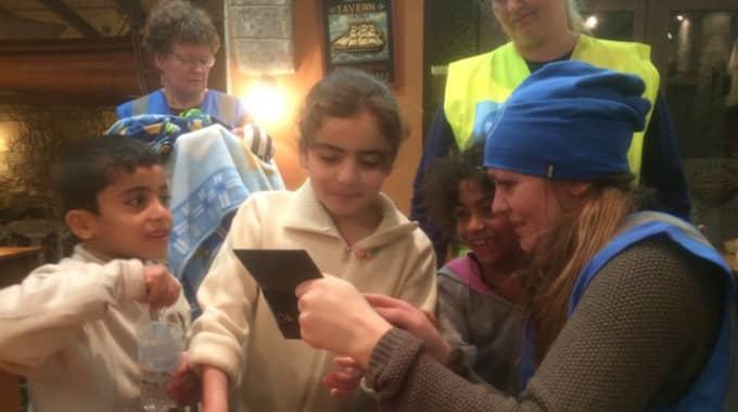 Spännande saker händer på Joanna Lindbergs mobil, som hon visar för de tre barnen från Syrien och Irak. Det är barnen som känns mest i hjärtat hos Joanna Lindberg, när hon jobbar som volontär på Kos. Foto: Privat