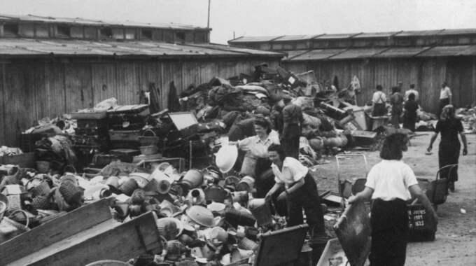 Bagage och ägodelar. Kvinnor sorterar fångarnas tillhörigheter som de tvingats lämna ifrån sig när de klev av godståget. Foto: Judiska museet