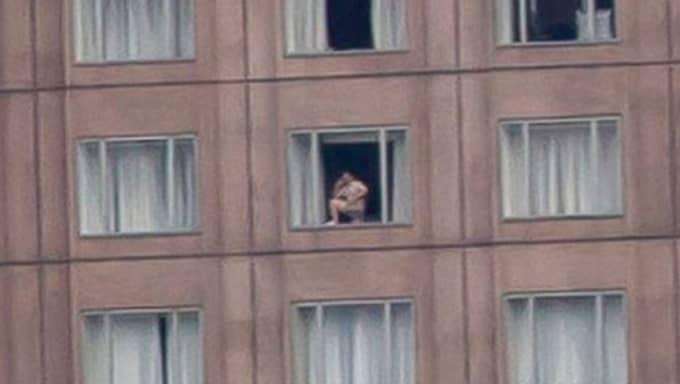 Från ett hotellfönster syns en man, med ena foten på fönsterbrädan, prata i telefon helt avslappnat – helt naken. Foto: Bix Pixel