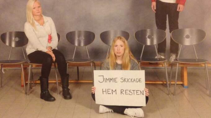 """Tre blonda elever, tomma stolar och skylten """"Jimmie skickade hem resten"""". Klassen på Hulebäcksgymnasiet utanför Göteborg tog ett annorlunda klassfoto, som nu hyllas och delas på nätet. Foto: Privat"""