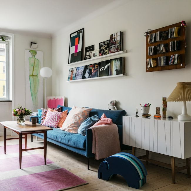 I det gemensamma hemmet finns Christins favoritfärg rosa kvar, men inte lika dominerande. Den turkosa soffan kommer från Adea, teakbordet är ett loppisfynd och Jetson-fåtöljen från Dux en bröllopspresent. Matta från Kateha.