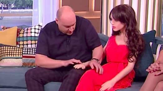 Pappa förklarar hur dockan fungerar. Foto: ITV