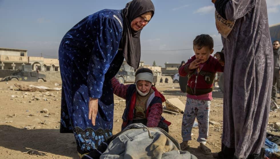 Den lilla flickan gråter förtvivlat intill båren där hennes döde far ligger. Hela familjen skadades vid en granatattack, men pappans liv gick inte att rädda. Foto: Niclas Hammarström
