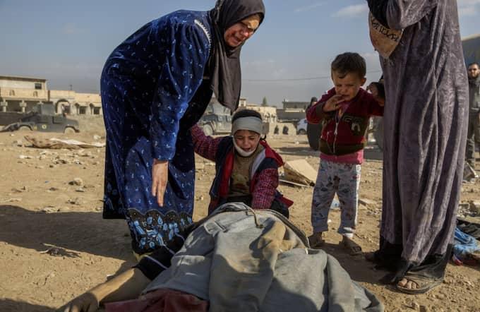 Den lilla flickan ser sin döda far och gråter förtvivlat. Hela familjen skadades vid en granatattack. Foto: Niclas Hammarström