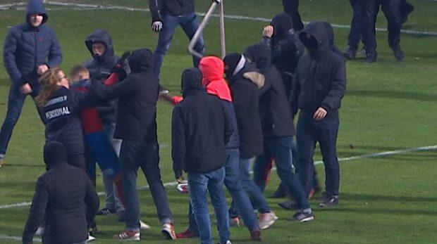 Maskerade män stormar planen - ger sig på Larsson