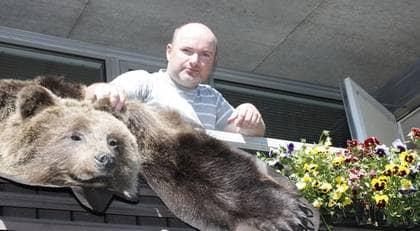 """BJÖRN PÅ TORK. Tomas Antonsson, 38, väcker viss uppmärksamhet när han hänger ut sin björnmatta på balkongräcket på Granvägen i Varberg. """"Jag hänger ut den under städningen"""", förklarar Tomas. Foto: Nils Wadström"""