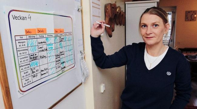 BALANS I TILLVARON. Lotta Abrahamsson med ett viktigt hjälpmedel: Veckokalendern i hallen. Hon tapetserar den inför varje ny vecka med saker hon ska göra. Grön färg är planerade saker som ger energi - orange färg tar energi. Personer med Aspergers syndrom har ofta svårt att organisera och planera tillvaron, men med hjälp av lappsystemet kan Lotta ha koll på sin vardag.