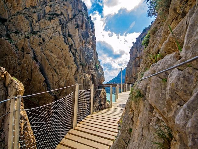 Caminito del Rey ligger på 100 meters höjd och går längs ravinen El Chorro med endast ett räcke som skiljer leden från de branta stupen.