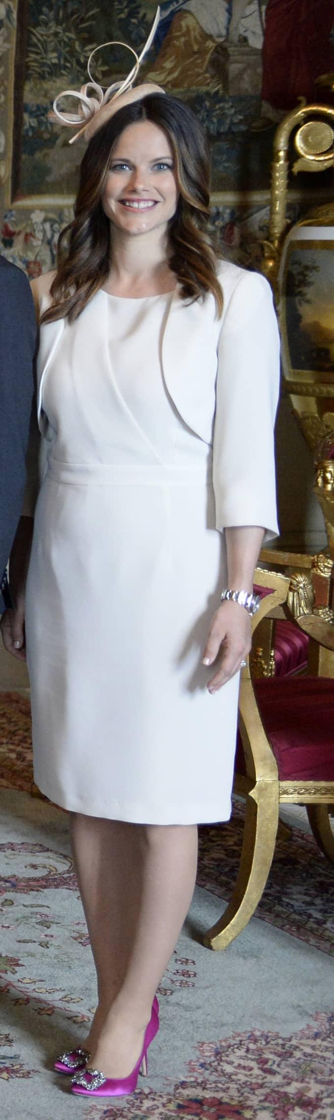 """""""Sofia ser sommarfin ut i sitt slimmade fodral med vackra veckade detaljer. Här visar hon dessutom hur rätt accessoarer kan lyfta hela stilen. De härligt färgstarka skorna är precis vad den här vita outfiten behöver. Snyggt!"""" Foto: Jessica Gow/Tt"""