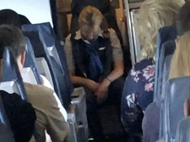 Passagerarna var tvungna att hjälpa flygvärdinnan med säkerhetsbältet innan hon tuppade av.