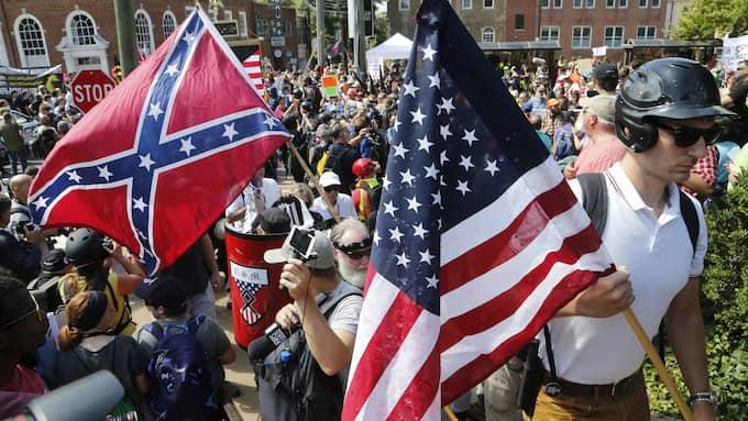 Vit makt-demonstranter använder sköldar i sammandrabbningar med motdemonstranter i Charlottesville i Virginia på lördagen. Foto: STEVE HELBER / AP TT NYHETSBYRÅN