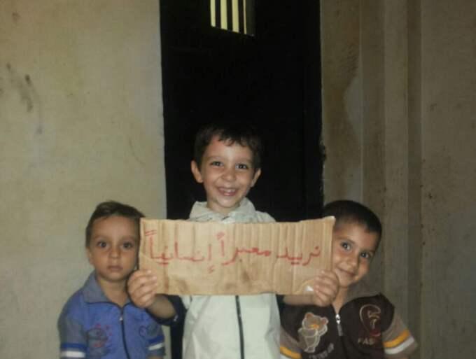 """Khaled, 5, i mitten med Ahmed, 8, och Samir, 4, håller upp en skylt som det vuxna har skrivit. Där står det: """"Vi vill ha humanitär korridor."""" Foto: Kassem Hamadé"""