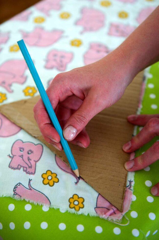 Gör en mall av en pappskiva. Rita upp flaggorna på tyget.