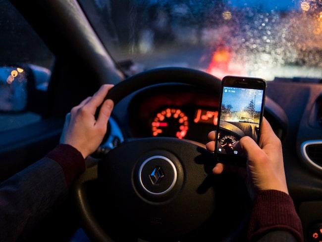 Trots att det nu är olagligt att använda mobilen så här i bilen fortsätter en hel del svenskar med det.