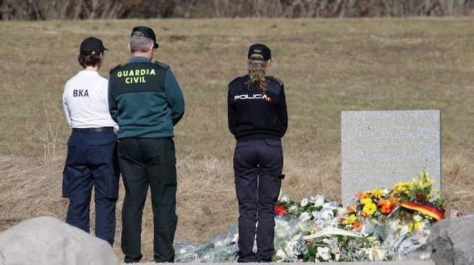 Spanska poliser lägger blommor nära platsen för kraschen för att hedra offren. Foto: Claude Paris