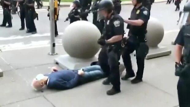 Här knuffar polisen 75-årige mannen så han slår huvudet i gatan