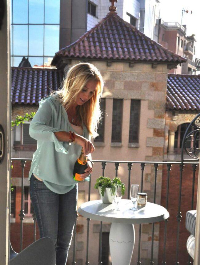 """NJUTER av semestern. Linda Lindorff byter gårdarna i """"Bonde söker fru"""" mot storstadspuls i Barcelona. Ett glas champagne på balkongen i lyxsviten är ett perfekt sätt att inviga tjejhelgen på."""