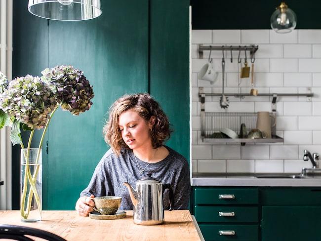 Klara med en kopp te i sitt färgstarka, gröna kök.