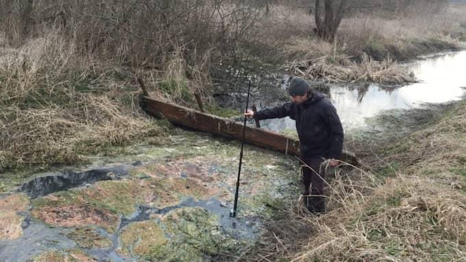 """Här sänker Expressens fotograf Jonte Wentzel kameran i det """"renade"""" avloppsvattnet i Polessk. Bakom honom syns den slarvigt monterade barriären som är det enda skyddet mellan avloppsvattnet och Östersjön."""