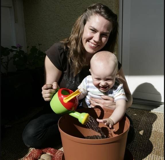 """ODLAR. Anna Sundström, 30, och sonen William, 9 månader, sätter midsommarpotatis på balkongen. """"Det ska bli kul att få skörda egenodlad potatis"""", säger Anna."""