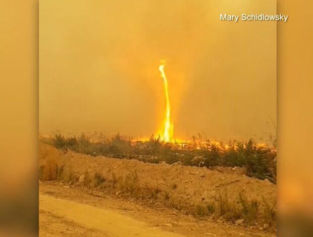 Den 60 meter höga eldtornadon tar kontroll över brandmännens slang