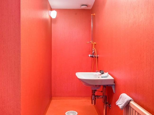 Duschrum täckt med röd våtrumstapet – minst sagt bländande.