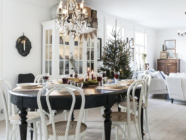 Bordet är en av Marias absoluta favoritmöbler. Hon hittade det i ett av uthusen på gården när de flyttade in. Ljuskronan är köpt på Bettys i Borås. Öglanstolarna är ett av Marias senaste fynd då hon kom över åtta stycken likadana med rottingsits på en loppis i närheten.