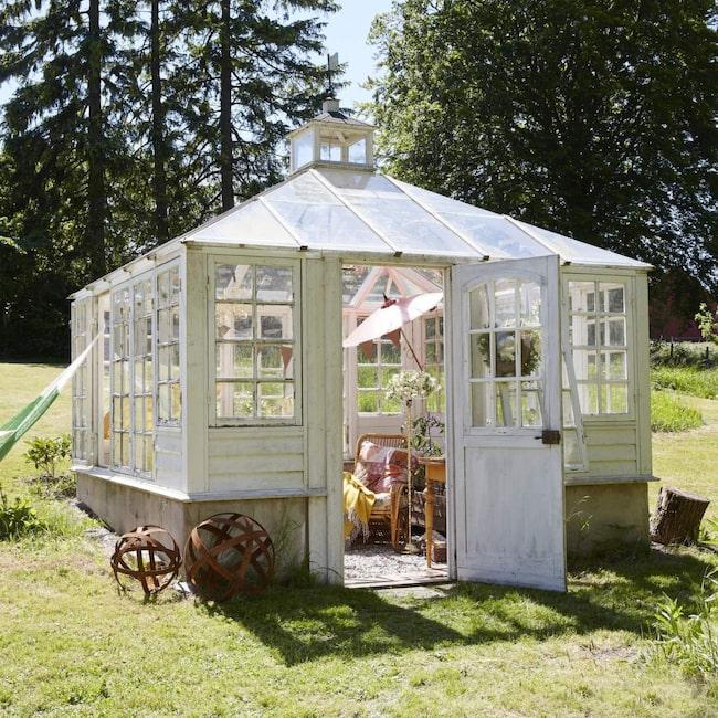 Det är viktigt att hitta den bästa platsen för växthuset. Det kan kräva både tid och eftertanke. Här är placeringen i en liten backe i bortre ändan av trädgården där närheten till grönska i form av vackra träd och bärbuskar spelar stor roll.