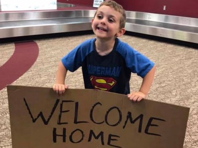 Barbaras son höll upp en stor handskriven välkomstskylt på flygplatsen när hon kom hem från en arbetsresa.