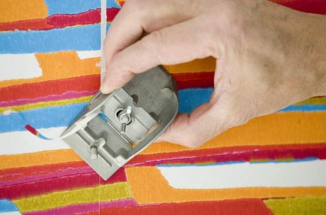 Ta bort skarvarna med en tapethyvel. Skär antingen mot skarven eller bakifrån skarven. Vad som fungerar bäst är beroende på tapet, prova dig fram.