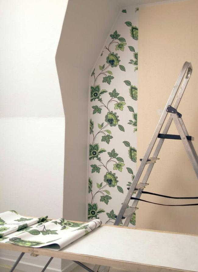 MÅLADE. Nu är väggarna vitmålade och fondtapeten på väg upp. Ett enkelt ihopfällbart tapetseringsbord är bra att ha när våderna ska mätas och skäras till. Här ligger några våder på svällning och en våd sitter på plats.
