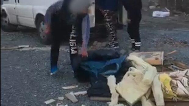 Här övervakas byggjobbare av polisen när de plockar upp skräpet de dumpat