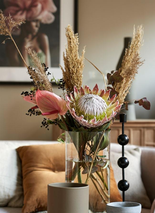 Blomstermix. Cylindervas i glas, 998 kr, Kristina Stark. Svart ljusstake Otto, 998 kr, Posh Living. Blommor, Floristkompaniet.