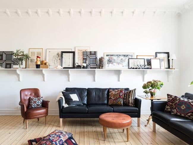 Strama mörka möbler möter mjuka former i vardagsrummet. Den vita vägghyllan med snirkliga konsoler, där bland annat missaleblad, notbladen, Carolines linoleumsnitt, spännramar med tapet, etsningar och grafiska blad med ramar binder ihop inredningen.