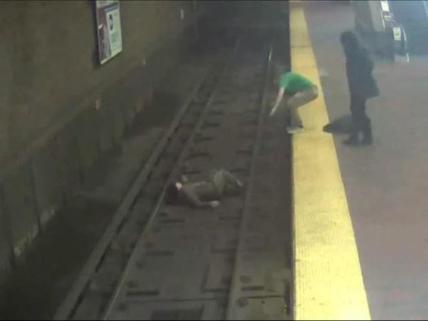 Mannen tuppar av och faller ner på spåret