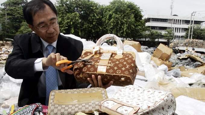 Frestelsen kan vara stor att köpa en piratkopierad märkesväska på semestern. Men dyker du sedan upp i ''fel'' land kan du få rejäla böter eller i värsta fängelse. Här har en thailändsk tullare börjat granska falska Louis Vuitton-väskor. Foto: SAKCHAI LALIT / AP