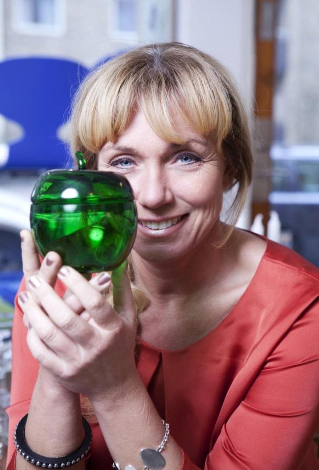 Anne detaljgranskar en vacker skål med lock i form av ett äpple i glas från Lindshammars glasbruk.