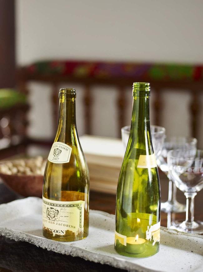 Ljuslyktor<br>Ta ett par vinbuteljer och skrapa loss etiketterna slarvigt så att de får rätt patina. Placera värmeljus på ett eldtåligt underlag och sätt över flaskorna. Se i faktarutan hur du skär av botten på glasflaskan.