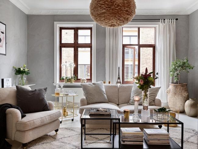 Vardagsrumet hemma hos Josefin är inrett i en härlig mix av rufft och mjukt där de gråmålade väggarna tillsammans med de mörka fönsterbågarna blir en rustik inramning åt inredningen. Lampan i taket är en Eos från Vita Copenhagen.