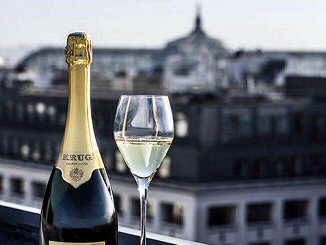 Ett glas champagne med utsikt över Paris takåsar är sann njutning för en livsnjutare.