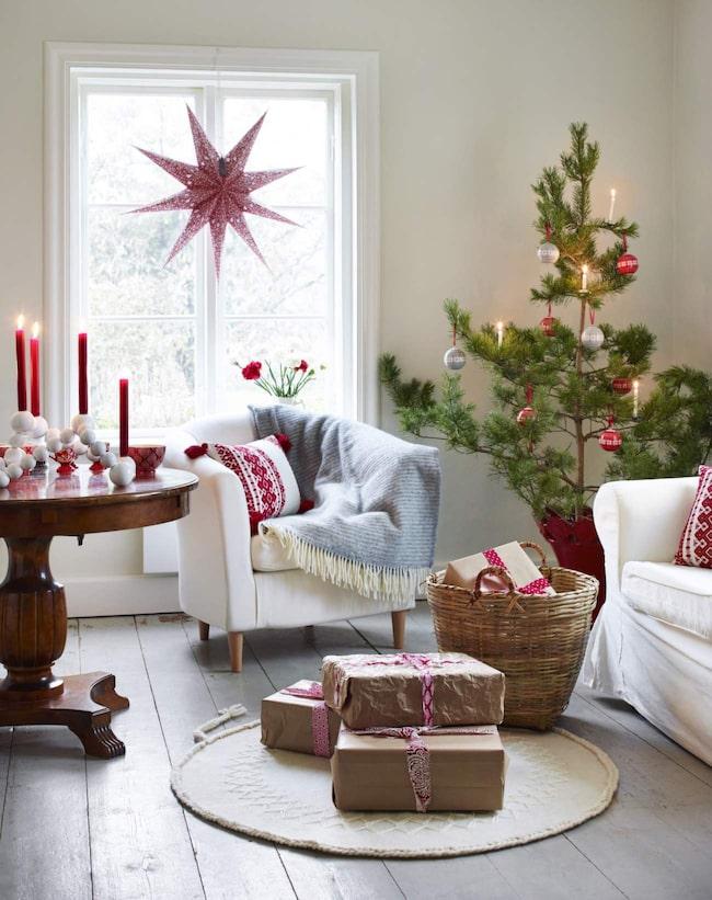 Vardagsrum. Härlig julstämning i vardagsrummet med en liten tall, sköna plädar, en ljuvlig ullmatta och vackra adventsstjärnor. Soffa, 3 995 kronor, fåtölj, 1 095 kronor, Ikea. Grå pläd, 625 kronor, röd pläd, 649 kronor, Klippan. Broderad kudde, 249 kronor, Indiska. Korg, 159 kronor, Granit. Matta, 1 295 kronor, Heart of Lovikka. Bordet är köpt på Blocket för 350 kronor. Adventsstjärna, 129 kronor, Indiska. Tallen står i en stor keramikkruka av Mikaela Willers för 6 900 kronor.
