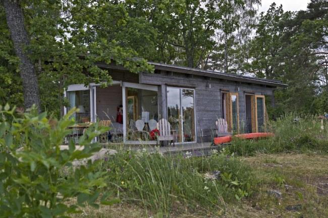 Sommarstugan. Det är nästan så att Åsas och Stefans sommarstuga försvinner bland träd och grönska. Huset levererades som en legosats och på en vecka hade de tak, fönster och ett vädertätt skal på plats.