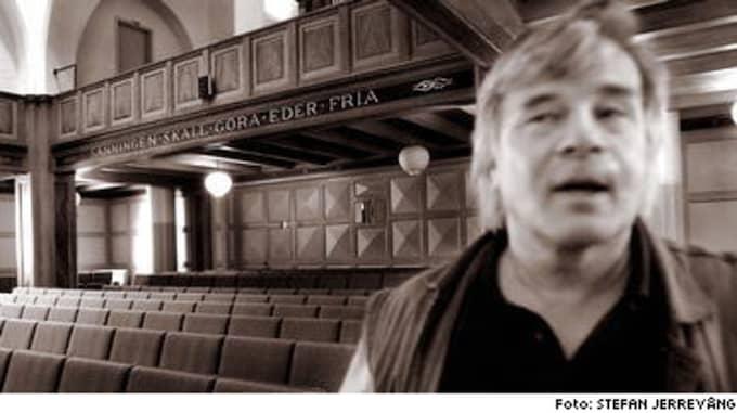 """SANNINGEN SKA GÖRA EDER FRIA. Jan Guillou besöker aulan i sin gamla skola Vasa Real. Orden i bakgrunden rimmar illa med anklagelserna om att författaren ska ha ljugit om sin uppväxt och om tiden på skolan i sin bok """"Ondskan""""."""