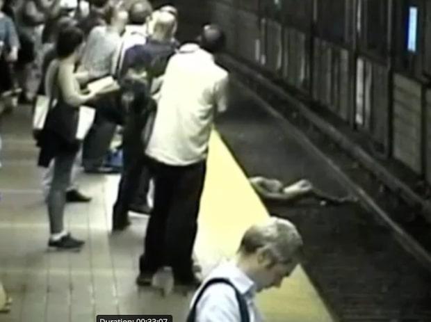 Kvinnan svimmar och faller ner på järnvägsspåret