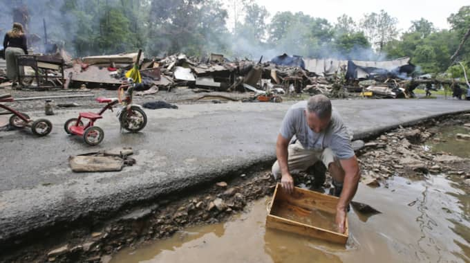 En flodvåg har dragit fram i amerikanska West Virginia, minst 14 personer har omkommit. Foto: Steve Helber / AP TT NYHETSBYRÅN